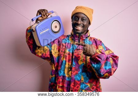 Young african american man listening to music holding portable vintage retro radio very happy pointing with hand and finger