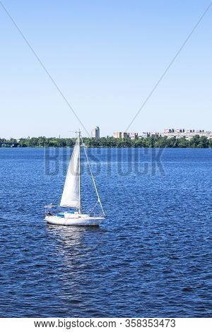 Sailing Yacht With A White Sail On The River In The City.