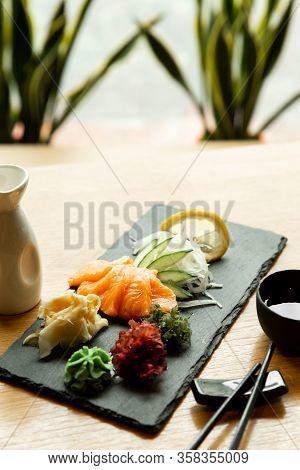 Salmon Sashimi On Restaurant Table. Asian Man Eating Sashimi Set In Asian Restaurant.