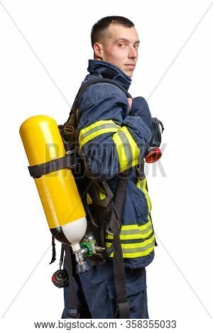 Young Caucasian Firefighter Posing In Profile With Full Facepiece Respirator And Breathing Air Cylin