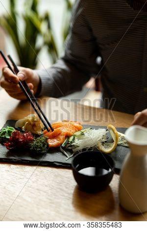 Man Holding A Chopstick With Salmon Sashimi On Restaurant Table. Asian Man Eating Sashimi Set In Asi