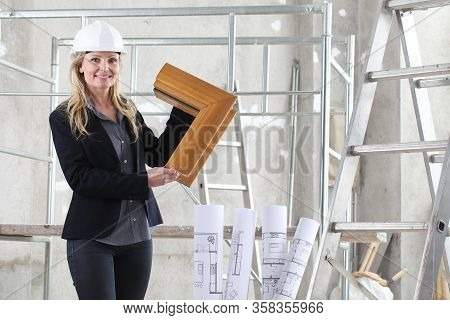 Smiling Woman Architect Or Construction Interior Designer With Wooden Windows Cutaway Inside A Build