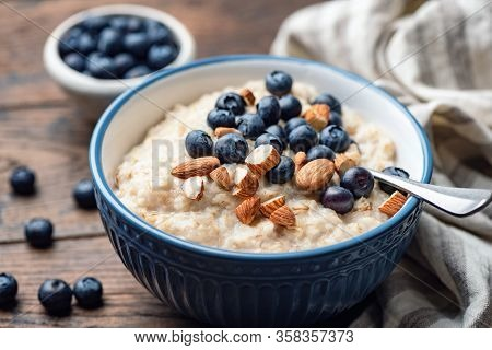 Oatmeal Porridge With Blueberries And Almonds. Healthy Breakfast Porridge Oats On A Wooden Table. Cl