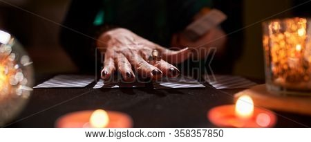 Female fortune-teller's hands, fortune-telling cards, ball of predictions on black table