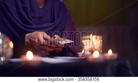 Close-up of soothsayer woman guessing on cards sitting at table with burning candles, magic ball