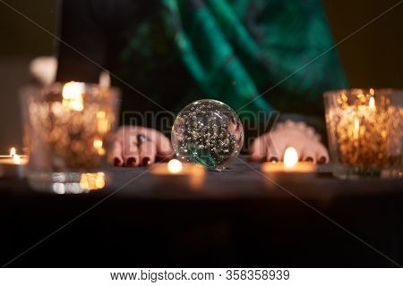 Fortuneteller woman divining on magic ball at table with burning candles