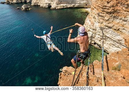 Rope Jumping Off A Cliff With A Rope In The Water. The Ocean. Sea. Mountain