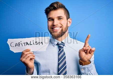 Young blond businessman with beard and blue eyes holding paper with capitalism message surprised with an idea or question pointing finger with happy face, number one