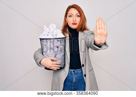 Young beautiful redhead businesswoman holding full paper bin with crumpled papers with open hand doing stop sign with serious and confident expression, defense gesture