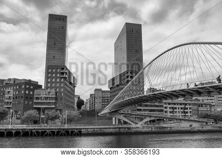 Bilbao, Spain, July 29, 2018: Zubizuri Pedestrian Bridge And Isozaki Atea Skyscraper In Bilbao In Bl