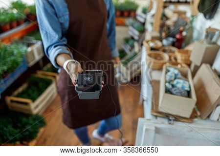 Florist With A Pos Machine In Her Hand