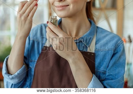 Contented Caucasian Plant Scientist Smelling Dried Herbs