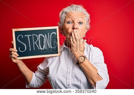 Senior beautiful woman holding blackboard with strong message over isolated red background cover mouth with hand shocked with shame for mistake, expression of fear, scared in silence, secret concept
