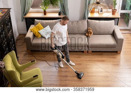 Young man in casualwear doing domestic work while cleaning floor in living-room with vacuum cleaner between armchair and couch