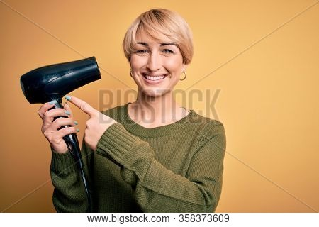 Young blonde woman with short hair drying her hair using hairdryer over yellow background very happy pointing with hand and finger