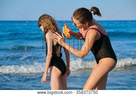 Mother And Daughter In Swimsuits On Beach, Parent Applies Sunscreen Creams With Spf To Child, Blue S