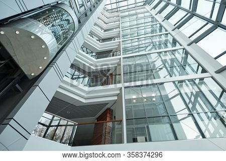 Part of interior of contemporary office center with people in elevator moving upwards, balconies, walls and windows