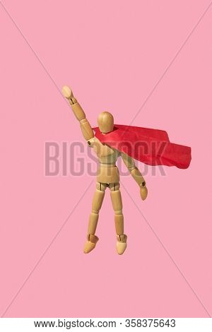 Movable miniature articulation mannequin in a red cape is flying up with raised hand as a superhero against pink background, copy space. Business success and leadeship concept.
