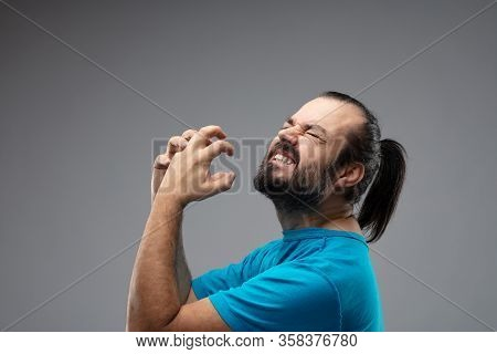 Bearded Man With Combed Black Hair Showing Grimace Of Pain With His Both Hands Up In Front Of His Fa