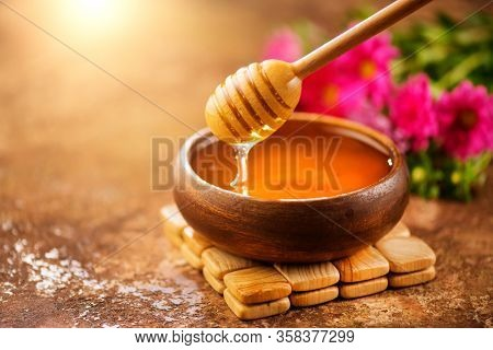 Honey dripping from honey dipper in wooden bowl.  Close-up. Healthy organic Thick honey dipping from the wooden honey spoon, closeup.