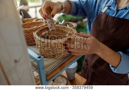 Herbalist Taking A Small Bottle Out Of A Basket