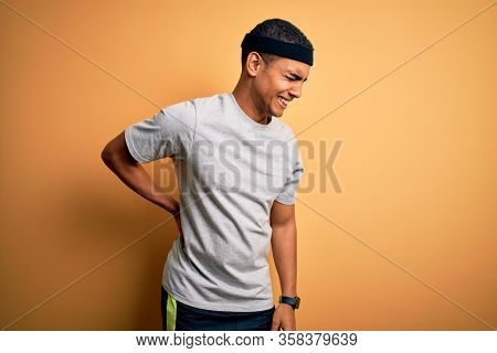 Handsome african american sportsman doing sport wearing sportswear over yellow background Suffering of backache, touching back with hand, muscular pain