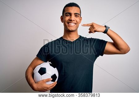 Handsome african american man playing footbal holding soccer ball over white background smiling cheerful showing and pointing with fingers teeth and mouth. Dental health concept.