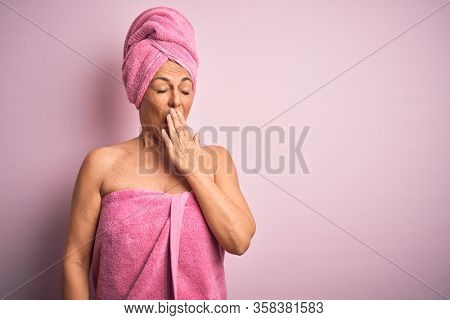 Middle age woman wearing bath towel from beauty body care over pink background bored yawning tired covering mouth with hand. Restless and sleepiness.