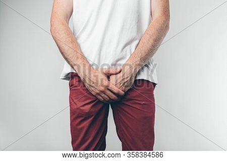 Caucasian Man In White T-shirt And Burgundy Pants. Holds His Hands On Groin. Cut View. Concept. Isol