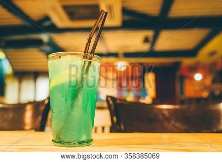 Green Tasty Alcohol Or Non-alcohol Cocktail With Ice And Piece Of Lemon Inside. Stand On Table. Bar