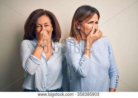 Middle age beautiful couple of sisters standing over isolated white background smelling something stinky and disgusting, intolerable smell, holding breath with fingers on nose. Bad smell