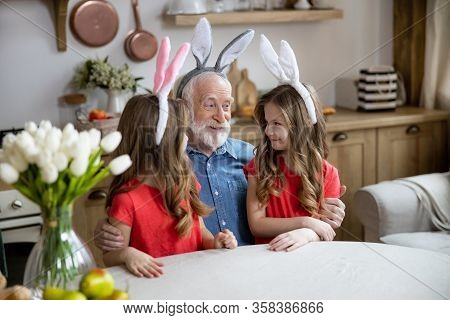 Mirthful Aged Man With His Granddaughters Stock Photo