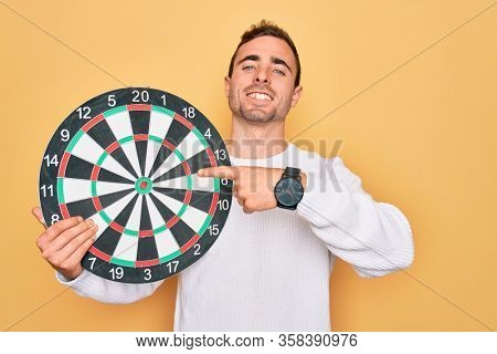 Young handsome man with blue eyes holding dartboard over isolated yellow background very happy pointing with hand and finger