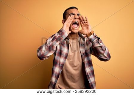 Young handsome african american man wearing casual shirt standing over yellow background Shouting angry out loud with hands over mouth
