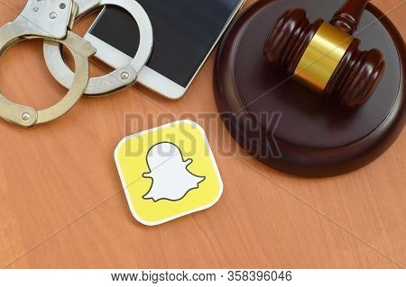 Snapchat Paper Logo Lies With Wooden Judge Gavel, Smartphone And Handcuffs. Entertainment Lawsuit Co