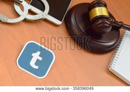 Tumblr Paper Logo Lies With Wooden Judge Gavel, Smartphone And Handcuffs. Entertainment Lawsuit Conc