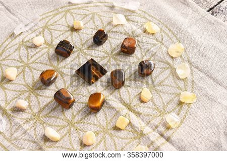 A Close Up Image Of A Crystal Prosperity Grid Using Sacred Geometry, Tigers Eye, Citrine, And Clear