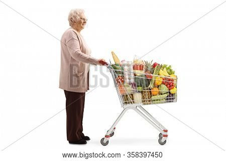 Full length profile shot of an elderly lady with a shopping cart full of food isolated on white background