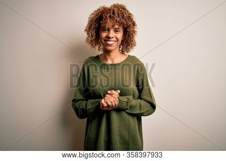Beautiful african american woman with curly hair wearing casual sweater over white background with hands together and crossed fingers smiling relaxed and cheerful. Success and optimistic
