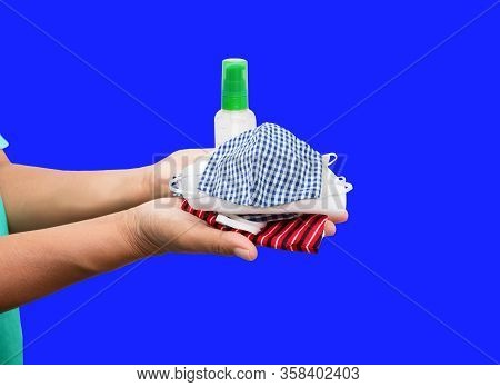 Mask Fabric Prophylaxis Virus Homemade Pile And Bottle Gel Alcohol On Hand Over Blue Background. Pre