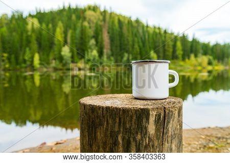 White Campfire Enamel Coffee Mug Mockup Witn The Tree Stump And River Bank View. Empty Mug Mock Up F