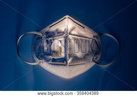 N95 Mask On White Table With Dramatic Contrasty Blue Tone Lighting, Health Concept