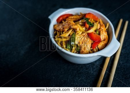 Asian Noodles With Chicken Meat And Vegetables On Black Stone Table