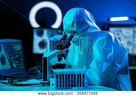Scientist In Protection Suits And Masks Working In Research Lab Using Laboratory Equipment: Microsco