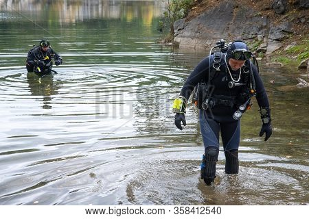 Lake Paayanne, Finland - September 2019. Divers Enter The Lake. Fully Equipped Divers, Scuba Divers.