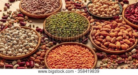 Legumes Assortment On A Brown Background. Lentils, Soybeans, Chickpeas, Red Kidney Beans, A Vatiety