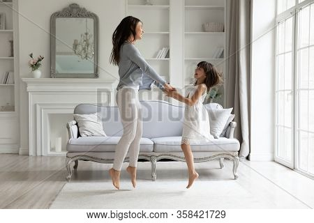 Overjoyed Young Mom And Small Daughter Dancing Together