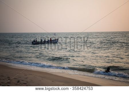 Kerala, India-February 3, 2019. Indian fishermen launch a traditional wooden boat into the sea