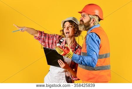 Woman And Man Safety Hard Hat. Redevelopment Of Home. Couple Look Documents. Couple Planning Changes