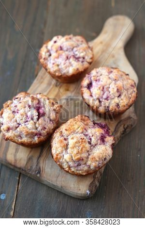 Homemade fruits muffins on a wooden board